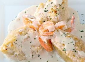 Coquilles farcies aux crevettes et au crabe dans une sauce crémeuse à l'ail